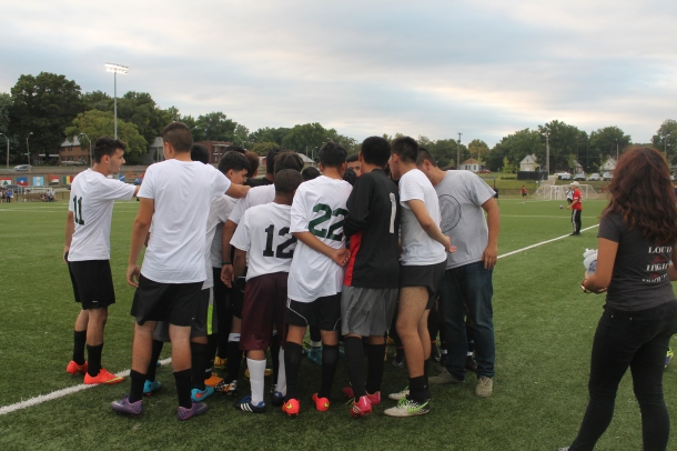 Coach Isao Osuga encourages the boys' soccer team at the end of a recent game.